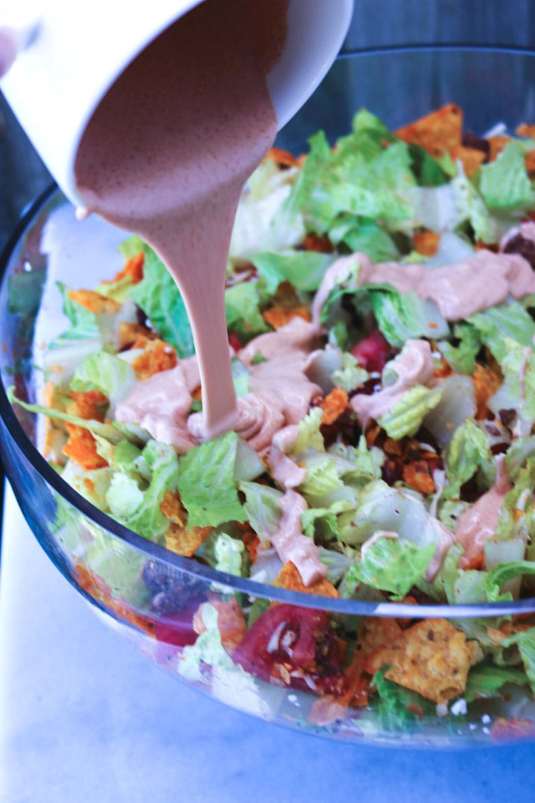 Pouring Taco Salad Dressing In Bowl