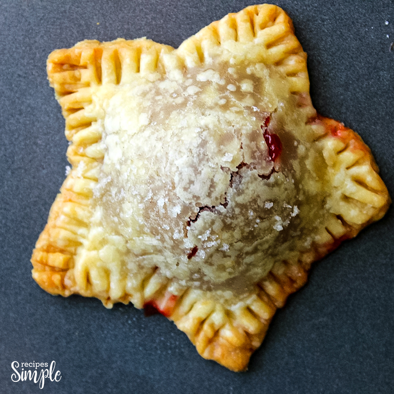 Star Shaped Mini Cherry Hand Pie on Baking Sheet With Sugar Sprinkled on Top