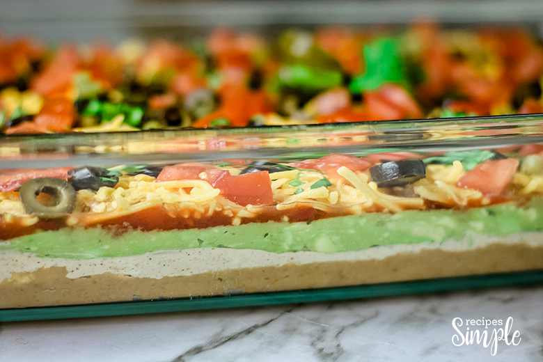 side view of Mexican layer dip in glass dish with 5 layers showing