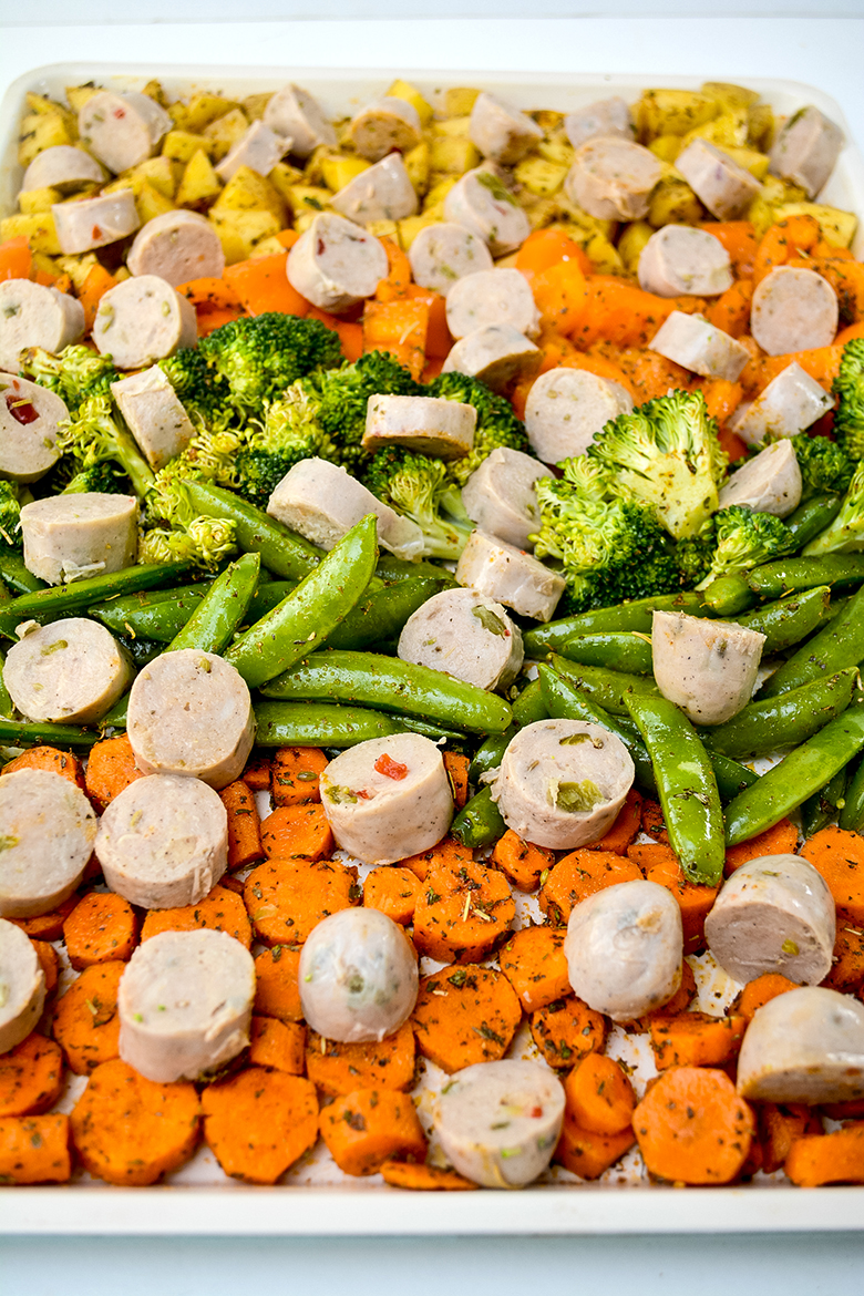 Chicken Italian sausage and vegetables on sheet pan ready to bake