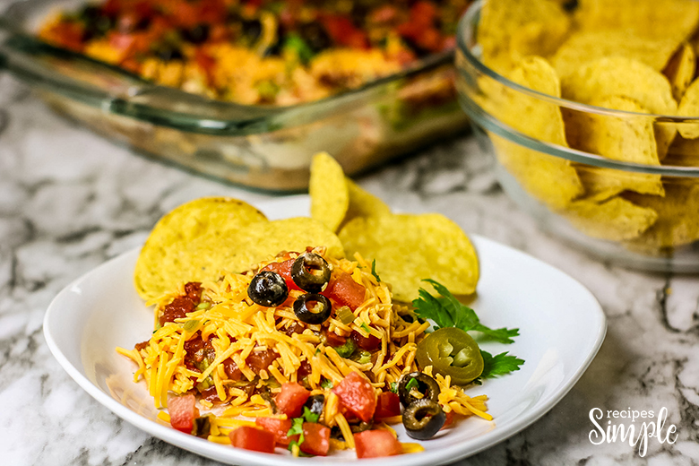Mexican Layer Dip on plate with tortilla chips