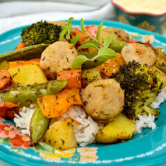 Paprika Herb Roasted Veggies and Sausage on top of rice on blue plate