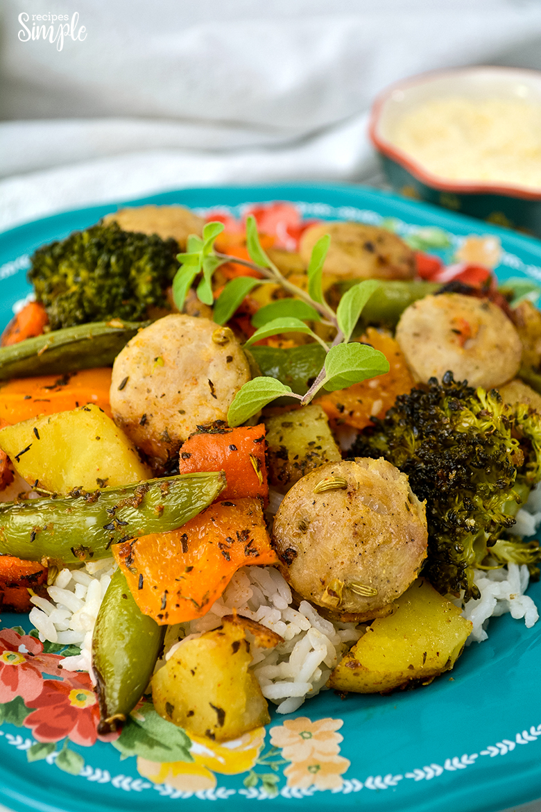 Paprika Herb Roasted Veggies and Sausage on blue plate served over rice