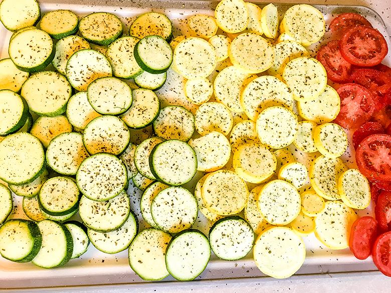 Seasoned Sliced Squash Zucchini Tomatoes on baking pan