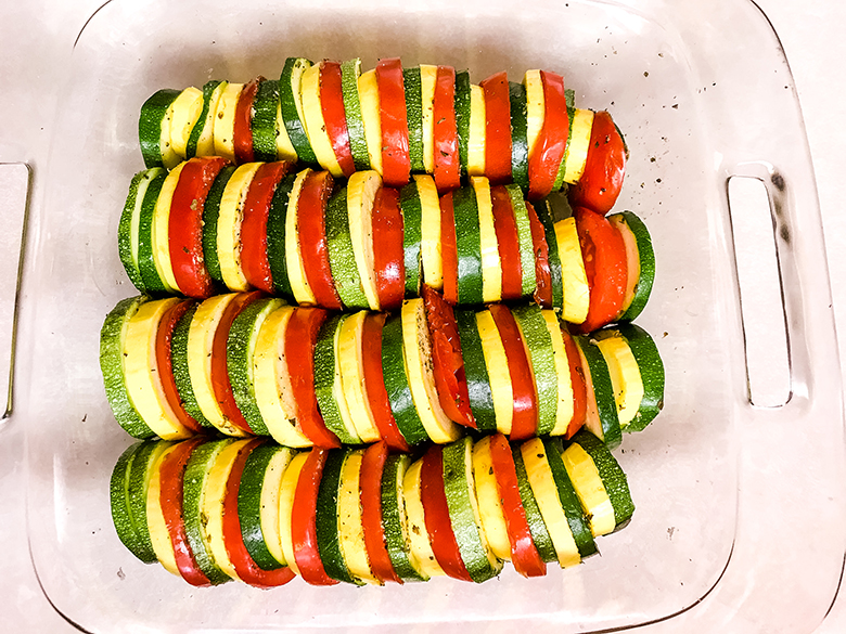 Stacked Sliced Squash Zucchini Tomatoes in glass baking dish