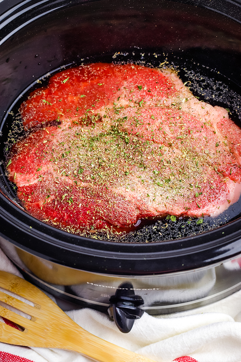 Uncooked Chuck Roast In Slow Cooker Sprinkled With Italian Seasoning
