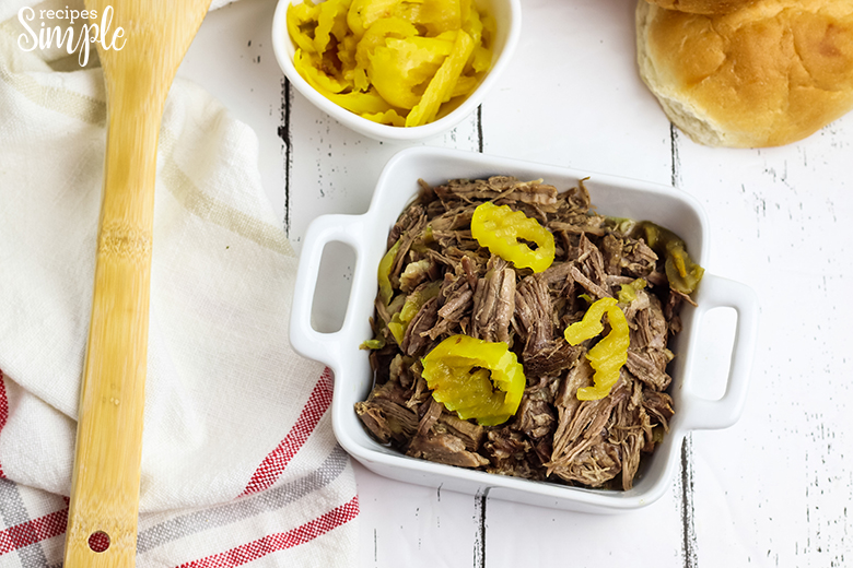Shredded Italian Beef in white bowl with sliced sliced banana peppers on top
