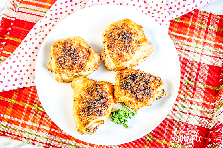 Four Cooked Chicken Thighs on white plaid with red plain napkin