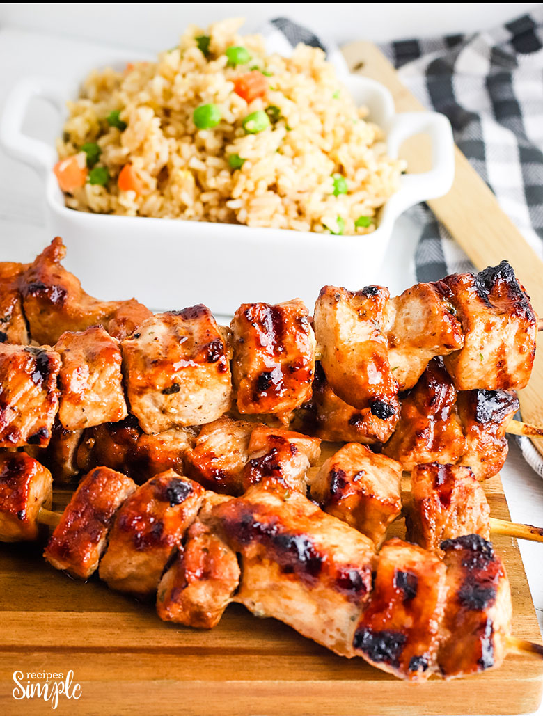 Asian Grilled Pork Kabobs Skewers on wood platter with fried rice in background