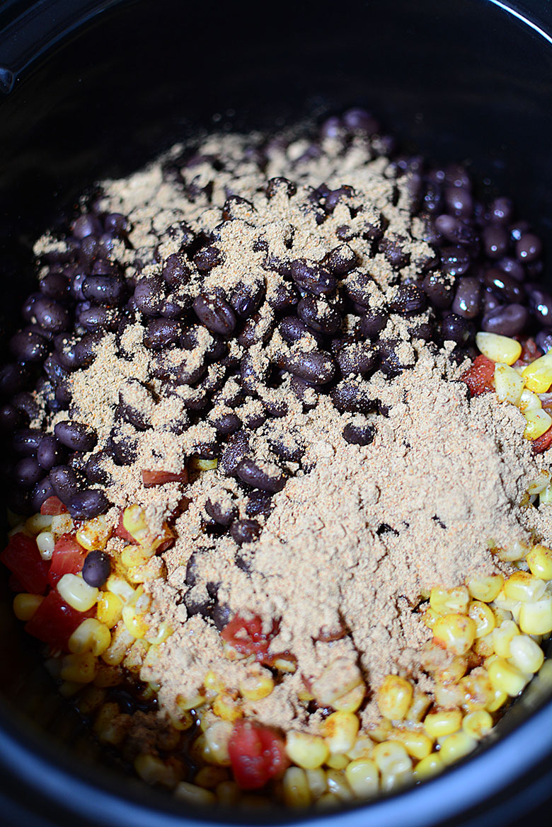 Chicken in slow cooker layered with onions beans corn and seasoning