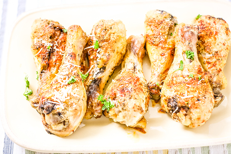 Parmesan Chicken Legs on white platter ready for serving
