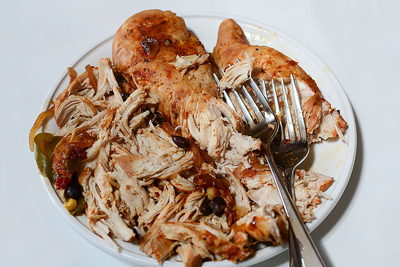 Cooked chicken breasts on plate being shredded with two forks