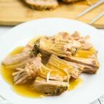 Pork Tenderloin with Gravy poured over it on white plate