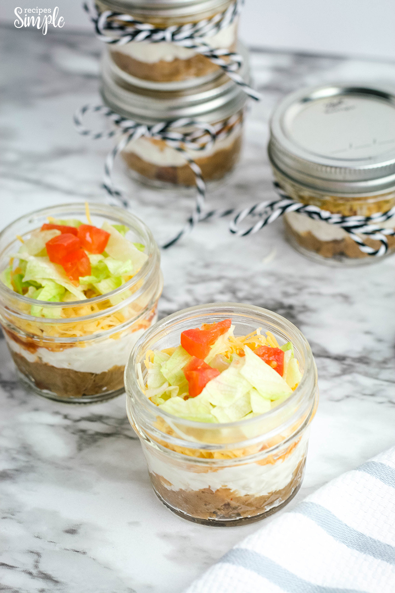 Layered Taco Dip In A Small Jar topped with lettuce and tomatoes
