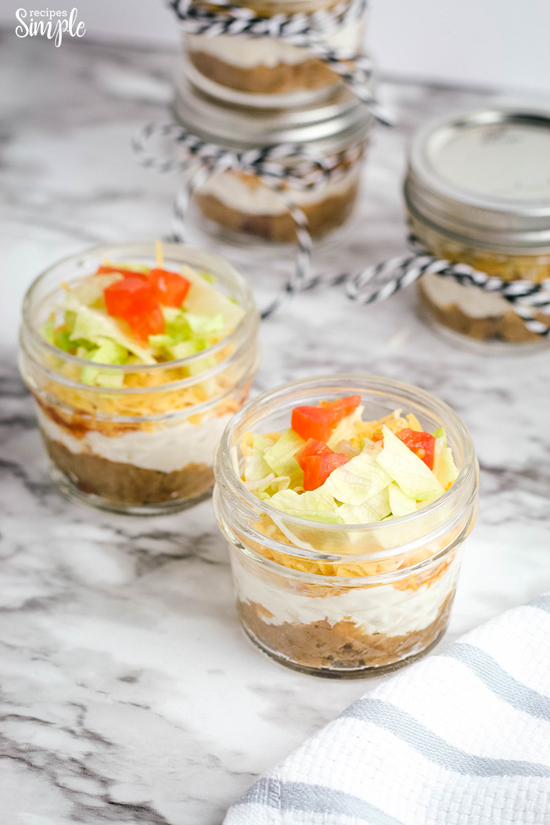 Layers of refried beans, sour cream, cream cheese, tomotes, lettuce and cheese in small mason jars