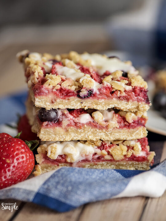 Mixed Berry Oatmeal Bars Stacked On Blue white Checkered Napkin