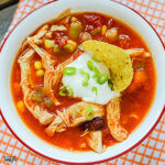 Chicken Taco Soup in bowl topped with sour cream and green onions